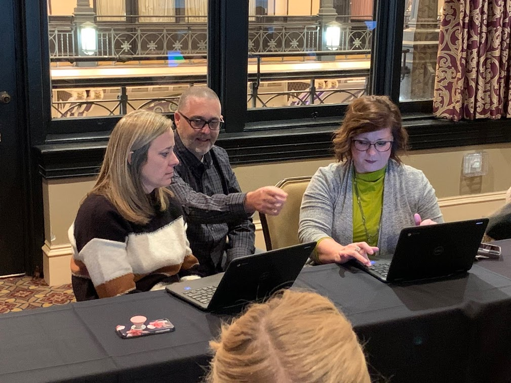 ATAC Director Mike Marotta showing two educators how to use built in accessibility features of a Chromebook.