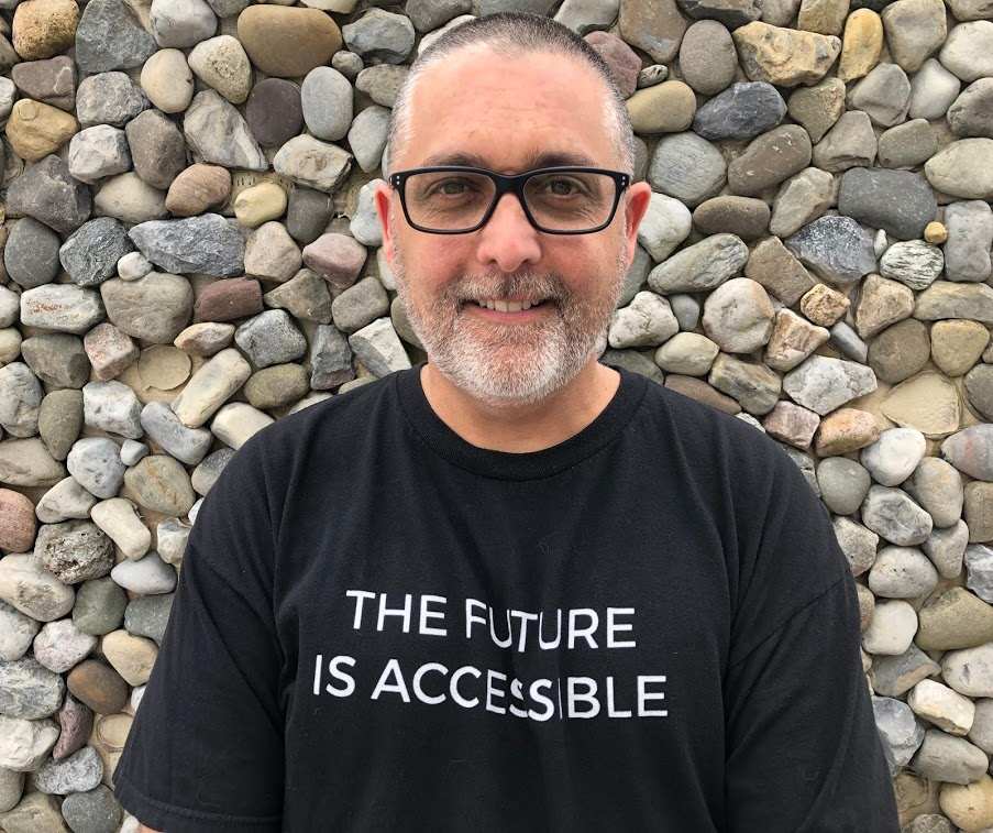 "Mike standing in front of a stone wall wearing a black t shift with the words ""The future is accessible"" printed on the front."